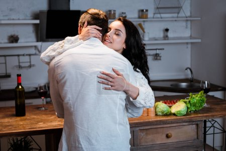 Photo for Woman with closed eyes embracing man at kitchen in evening - Royalty Free Image
