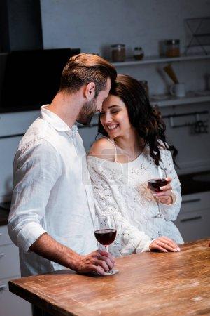 Photo pour Couple heureux tenant des verres à vin avec du vin rouge et embrasser doucement à la cuisine - image libre de droit
