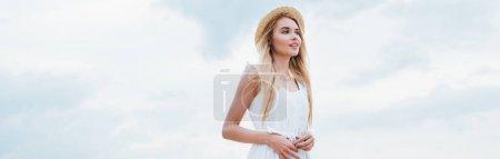 Photo pour Tir panoramique de la jeune femme attirante dans le chapeau de paille et la robe blanche - image libre de droit