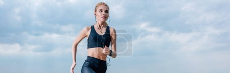 Photo for Panoramic shot of sportive blonde woman running and listening music in earphones - Royalty Free Image