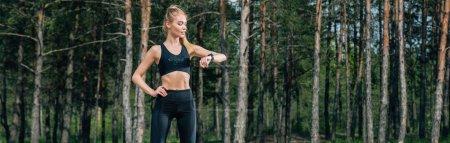 Photo pour Tir panoramique de femme athlétique restant avec la main sur la hanche et regardant le traqueur de forme physique - image libre de droit