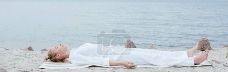 Photo for Panoramic shot of attractive blonde woman with closed eyes meditating while lying on yoga mat near sea - Royalty Free Image