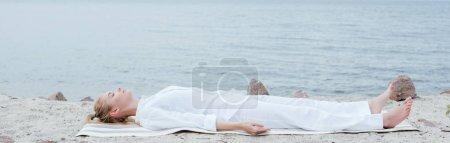 Photo pour Tir panoramique de la femme blonde attirante avec les yeux fermés méditant tout en se trouvant sur le tapis de yoga près de la mer - image libre de droit