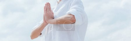 Photo pour Panoramic shot of young woman with praying hands near sky - image libre de droit