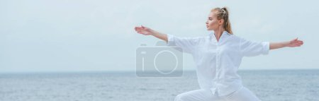 Photo pour Panoramic shot of attractive girl practicing yoga and standing with outstretched hands - image libre de droit