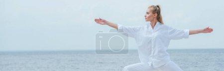 Photo pour Plan panoramique de fille attrayante pratiquant le yoga et debout avec les mains tendues - image libre de droit