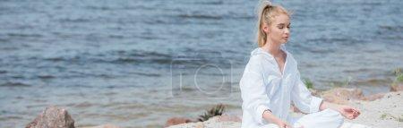 Photo pour Femme blonde paisible de projectile panoramique avec les yeux fermés pratiquant le yoga près de la rivière - image libre de droit
