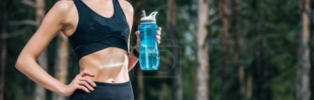 Photo for Panoramic shot of woman holding sport bottle while standing with hand on hip - Royalty Free Image