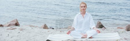panoramic shot of peaceful blonde young woman with closed eyes practicing yoga near river