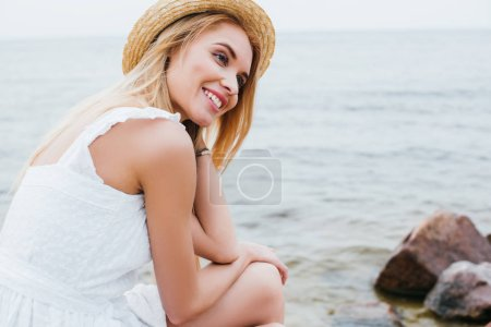 Photo for Cheerful blonde woman in white dress and straw hat smiling near sea - Royalty Free Image