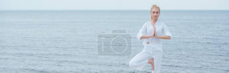 Photo pour Panoramic shot of young blonde woman with closed eyes practicing yoga - image libre de droit