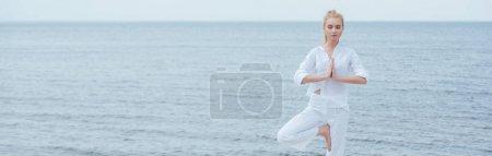Photo pour Tir panoramique de jeune femme blonde avec les yeux fermés pratiquant le yoga - image libre de droit