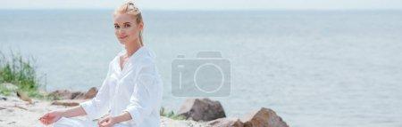 Photo pour Plan panoramique de femme blonde heureuse pratiquant le yoga - image libre de droit