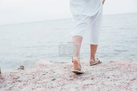 Photo for Cropped view of young woman in white dress and sandals standing near sea - Royalty Free Image