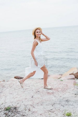 Photo pour Happy blonde girl smiling while touching straw hat and walking near sea - image libre de droit