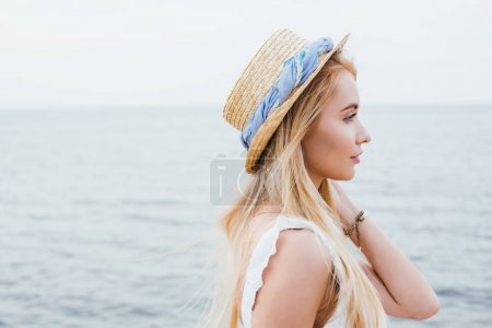 Photo pour Side view of attractive blonde young woman in straw hat near sea - image libre de droit