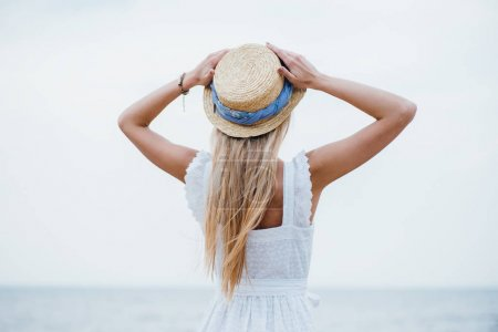 back view of young blonde woman standing and touching straw hat
