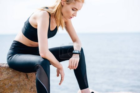 exhausted blonde sportswoman sitting on stone near sea and looking at fitness tracker