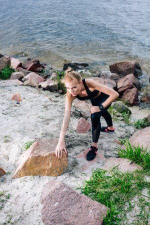 Photo for Overhead view of beautiful blonde sportswoman in sportswear climbing near stones and sea - Royalty Free Image