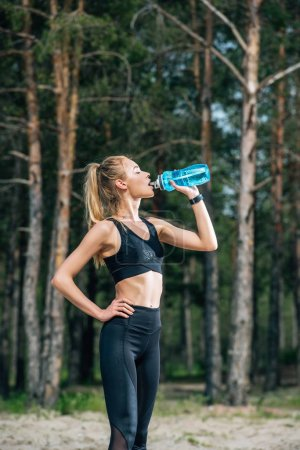 Photo for Attractive woman with closed eyes drinking water while standing with hand on hip - Royalty Free Image