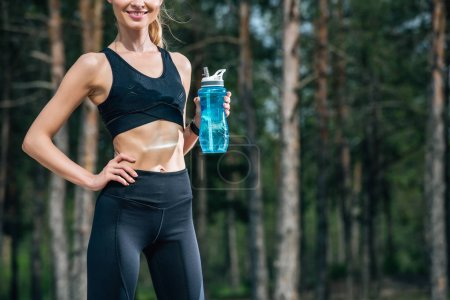 Photo pour Vue recadrée de femme athlétique gaie retenant la bouteille de sport tout en restant avec la main sur la hanche - image libre de droit