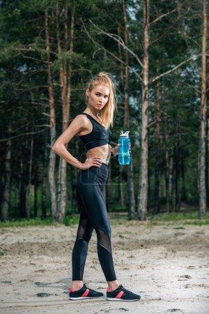 Photo pour Femme attirante retenant la bouteille de sport tout en restant avec la main sur la hanche - image libre de droit