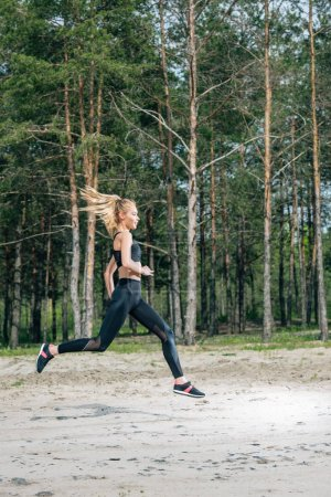 Photo for Beautiful and sportive blonde woman running near green trees - Royalty Free Image