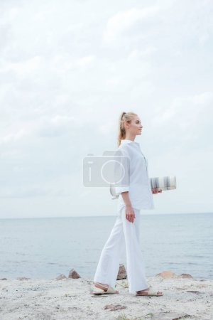 Photo pour Side view of cheerful young blonde woman standing near sea and holding yoga mat - image libre de droit