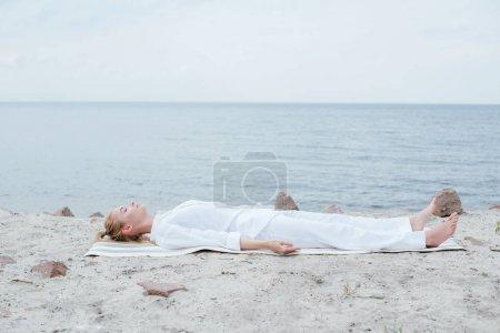 Photo pour Femme blonde attirante avec les yeux fermés méditant tout en se trouvant sur le tapis de yoga près de la mer - image libre de droit