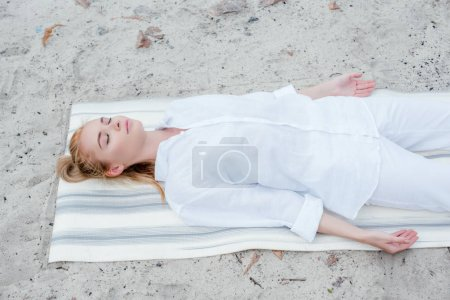 Photo for Overhead view of attractive blonde woman with closed eyes meditating while lying on yoga mat - Royalty Free Image