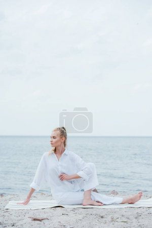 Photo for Attractive woman stretching while sitting on yoga mat near sea - Royalty Free Image