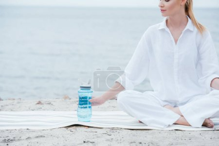 Photo for Cropped view of cheerful woman sitting on yoga mat near sport bottle - Royalty Free Image