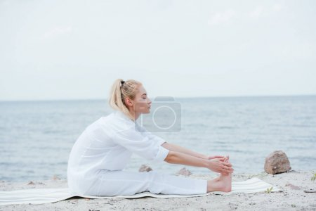 Photo pour Side view of attractive woman stretching while sitting on yoga mat near sea - image libre de droit