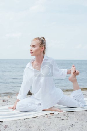 Photo for Beautiful blonde woman stretching on yoga mat near sea - Royalty Free Image