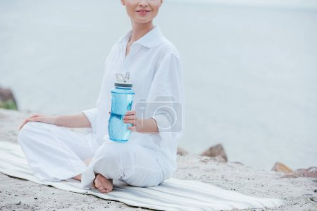 Photo pour Vue recadrée d'une femme joyeuse assise sur un tapis de yoga et tenant une bouteille de sport près de la mer - image libre de droit