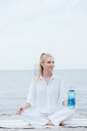Photo pour Femme blonde gaie retenant la bouteille de sport et s'asseyant sur le tapis de yoga près de la mer - image libre de droit
