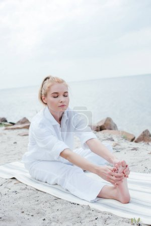 Photo for Attractive blonde woman with closed eyes stretching on yoga mat - Royalty Free Image