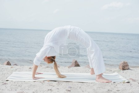 Photo pour Young blonde woman practicing yoga on yoga mat near sea - image libre de droit