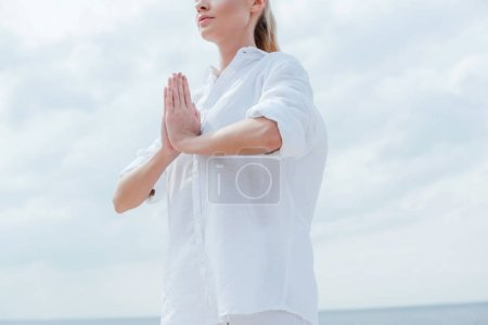 Photo pour Cropped view of woman standing with praying hands near sea - image libre de droit