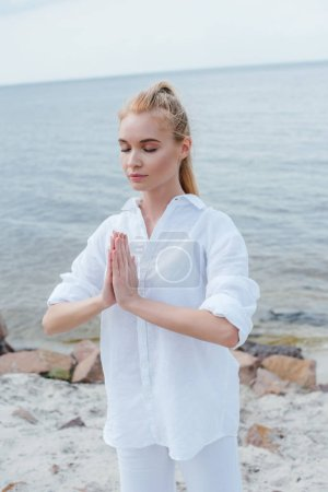 attractive young woman with closed eyes and praying hands near sea