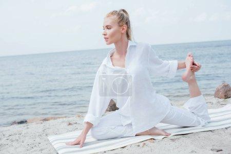 Photo pour Attrayant jeune femme blonde pratiquant le yoga sur tapis de yoga près de la mer - image libre de droit