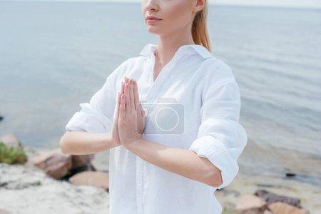 Photo pour Vue recadrée de la jeune femme avec les mains priantes près de la mer - image libre de droit
