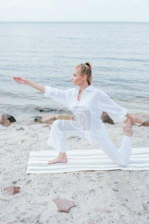 Photo pour Side view of attractive blonde woman practicing yoga on yoga mat near sea - image libre de droit