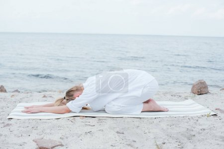 Photo for Blonde young woman relaxing and practicing yoga on yoga mat near sea - Royalty Free Image