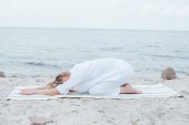 "Постер, картина, фотообои ""blonde young woman relaxing and practicing yoga on yoga mat near sea """