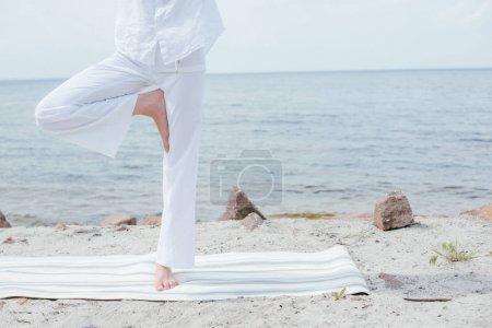 Photo pour Cropped view of young woman doing yoga near sea - image libre de droit