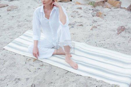Photo pour Cropped view of young woman sitting on yoga mat near sea - image libre de droit