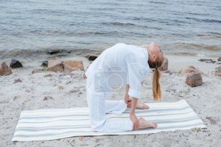 Photo pour Jeune femme blonde attirante faisant l'exercice de yoga près de la mer - image libre de droit
