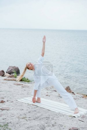 Photo pour Young woman with closed eyes practicing yoga on yoga mat near sea - image libre de droit