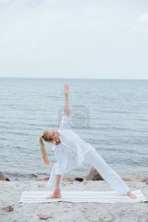 Photo pour Pretty girl with closed eyes practicing yoga on yoga mat near sea - image libre de droit
